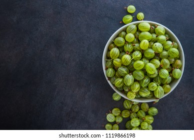 sweet fresh gooseberry berry in a bowl on dark stone background. top view