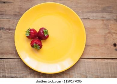 sweet fresh strawberry on yellow plate