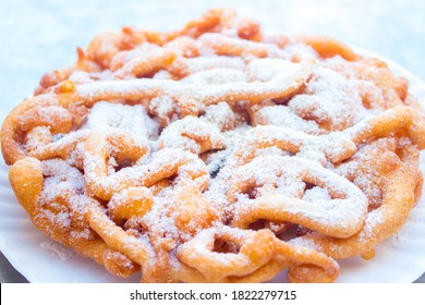 Sweet fried funnel cake, (fried dough) topped with powdered sugar at a summer festival.