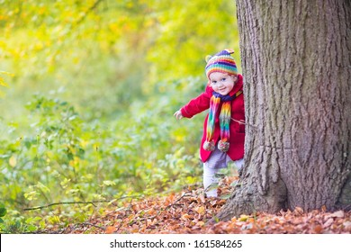 Sweet funny baby girl in a red coat and colorful hat and knitted scarf hiding behind a big old tree in a beautiful autumn park with yellow leaves
