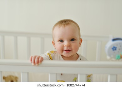 sweet and funny baby standing in the bed