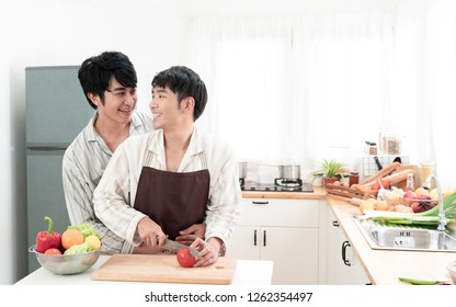 Sweet gay couple preparing a meal in kitchen at home