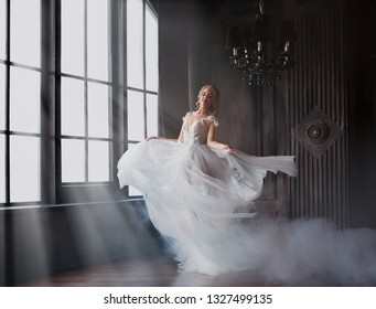 sweet and gentle girl with fair skin and blond hair dances alone in silence in an old castle, spirit of abandoned medieval building whirls in white smoke and magical thick fog in rays of sun