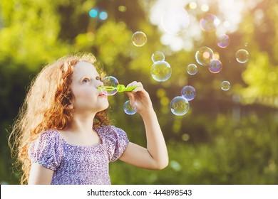 Sweet girl blowing soap bubbles.