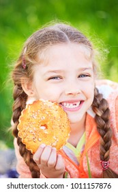 Sweet girl with a fallen toth holding cookies in her hand on nature