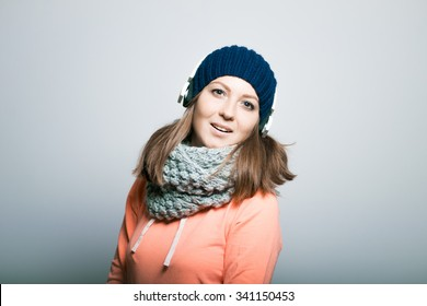 sweet girl listening to music on headphones, dressed in winter clothes. hipster, on a gray background