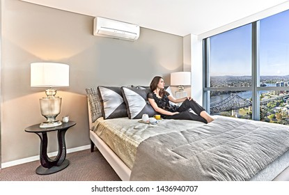 Sweet girl looking through windows and drinking coffee, a bridge with river can see from outside, she is relaxing also thinking something, pillows and bed sheets on the bed, lamp table near the wall.
