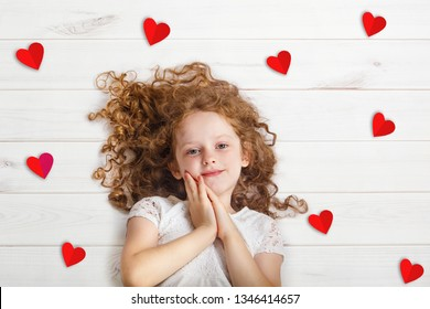 Sweet girl lying on wooden floor with red paper hearts. Valentines day or healthcare, medical concept.
