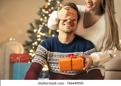 Sweet girl making a surprise to his boyfriend giving him a Christmas gift