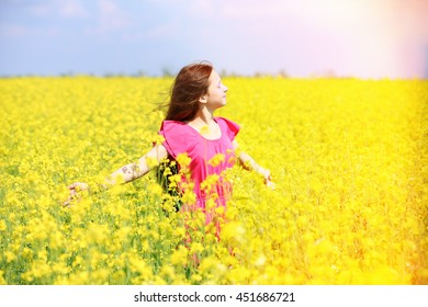 Sweet girl in meadow with wild spring flowers