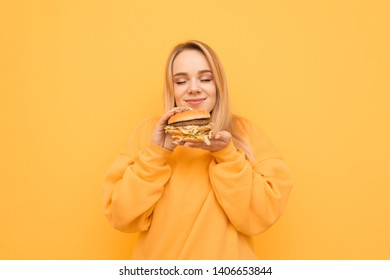 Sweet girl in orange clothes is standing on a yellow background,holding a fresh, appetizing burger in her hands, smelling the scent with eyes closed and smiling. Isolated