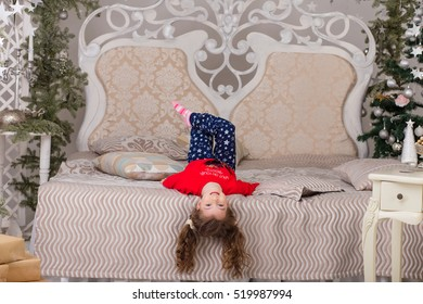 Sweet girl in pajamas getting ready for bed. The child indulges in bed before going to sleep