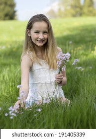 Sweet girl picking wild flowers for her mother