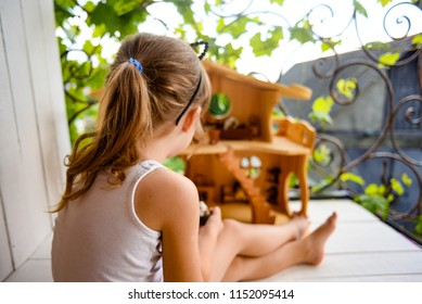 Sweet girl playing with her wooden dollhouse outdoors