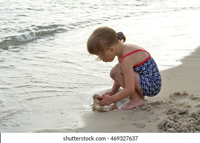 Sweet girl playing with sand on the seashore. Beautiful little girl playing on the beach.