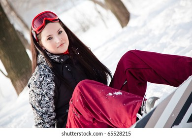Sweet girl with snowboard sits on snow