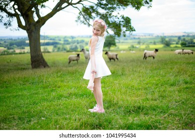 Sweet girl in a white dress standing in a meadow with sheep, looking cutely over shoulder, reminiscent of Little Bo Peep.