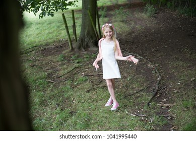Sweet girl in a white dress, standing on the edge of a wood in the countryside, smiling sweetly and holding her scarf round her neck.