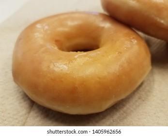 sweet glazed sugar donut on brown paper towel