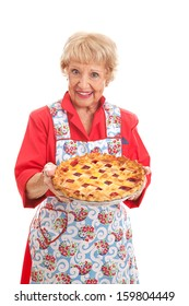 Sweet grandmother holding a delicious homemade cherry pie.  Retro look, isolated on white.