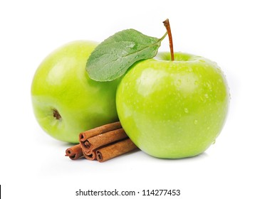 Sweet green apple with cinnamon rods on white
