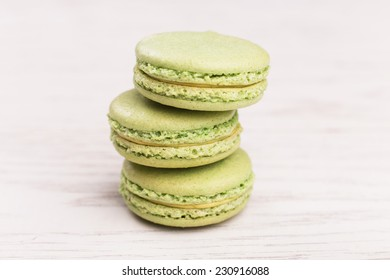 Sweet green macaroons on wooden table