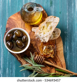 Sweet green olives in honey sauce, honeycombs, served on wood cutting board with bottle of olive oil, sliced bread and olive branch over turquoise texture background. Top view. Square image
