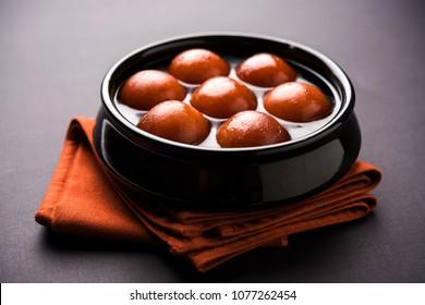 Sweet Gulab Jamun served in black ceramic bowl