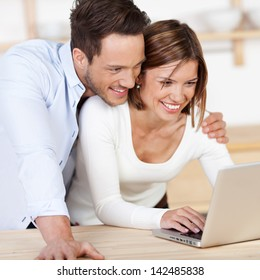 Sweet happy couple browsing the internet at the laptop