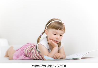 sweet happy little girl reading book