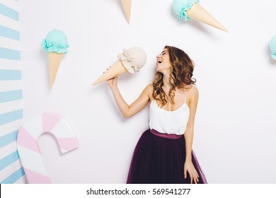 Sweet happy moments of attractive fashionable young woman in tulle skirt having fun with huge cone ice cream on white background. Dreaming,  delicious, enjoying, happiness, smiling