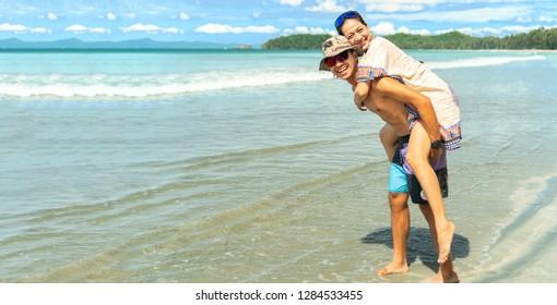 Sweet Happy romantic Asian couple walking on the beach.