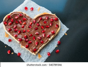 Sweet heart shaped pizza with fruits - pomegranate seeds and nutella or chocolate cream on dark background - Valentines day party creative art dessert idea, blank space for text