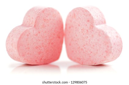 Sweet hearts shaped pink Sugar Pills on white background. Soft Focus.