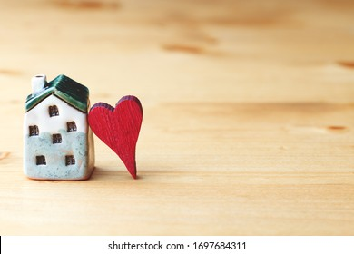 sweet home concept, mini house symbol and red heart on wooden background, copy space
