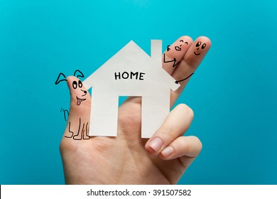 Sweet home. Hand holding white paper house figure on blue background. Real Estate Concept. Ecological building. Copy space top view.