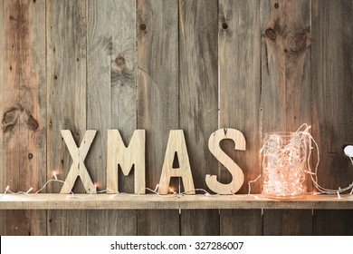 Sweet home. White Christmas decor and fairy lights on vintage natural wooden background.