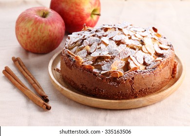 sweet homemade apple cake with almond in wooden plate