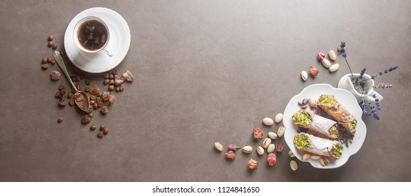 Sweet homemade cannoli stuffed with ricotta cheese cream and pistachios. Traditional Sicilian dessert. Italian pastry. selective focus. White cup of hot coffee. Dark background