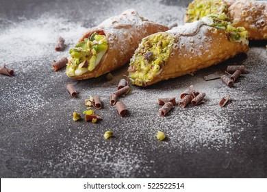 Sweet homemade cannoli stuffed with ricotta cheese cream and pistachial Sicilian dessert. Italian pastry.