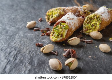 Sweet homemade cannoli stuffed with ricotta cheese cream and pistachial Sicilian dessert. Italian pastry