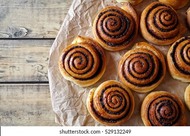 Sweet Homemade christmas baking. Cinnamon rolls buns with cocoa filling on parchment paper. Kanelbulle swedish dessert. Festive decoration with pine cones and Christmas tree