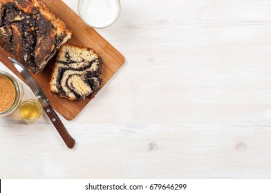 Sweet homemade poppy seeds braided (twisted) yeast bread with walnuts on a cutting board. Milk, cane sugar and honey in jars on a white wood background. Top view