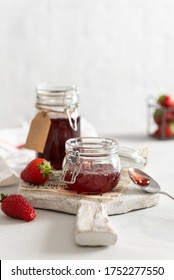 Sweet homemade strawberry jam in glass jars and fresh berries on white wooden board on rustic white background. Side view. Cookbook recipe. Social media content. Summer strawberry confiture