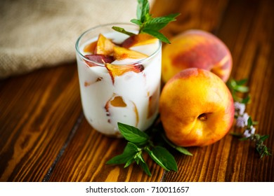 Sweet home-made yogurt with pieces of peach in a glass cup