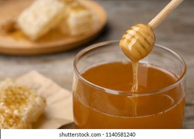 Sweet honey dripping from dipper into glass jar, closeup