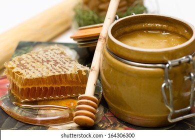 Sweet honey in pot with honeycomb and wooden stick