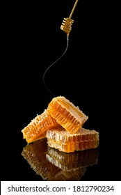 Sweet honeycomb and golden dipper with dripping honey on black background with reflection, bee products by organic natural food ingredients. Beekeeping advertisement, banner, vertical