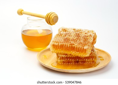 Sweet honeycomb and honey in glass jar with dipper, isolated on white