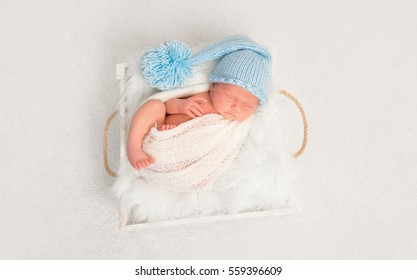 Sweet infant in a blue hat resting with his foot out of a covering blanket